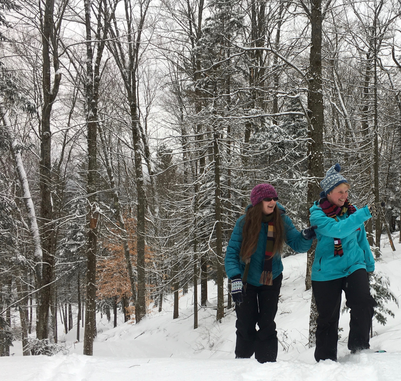 Two women snowshoeing on a trail